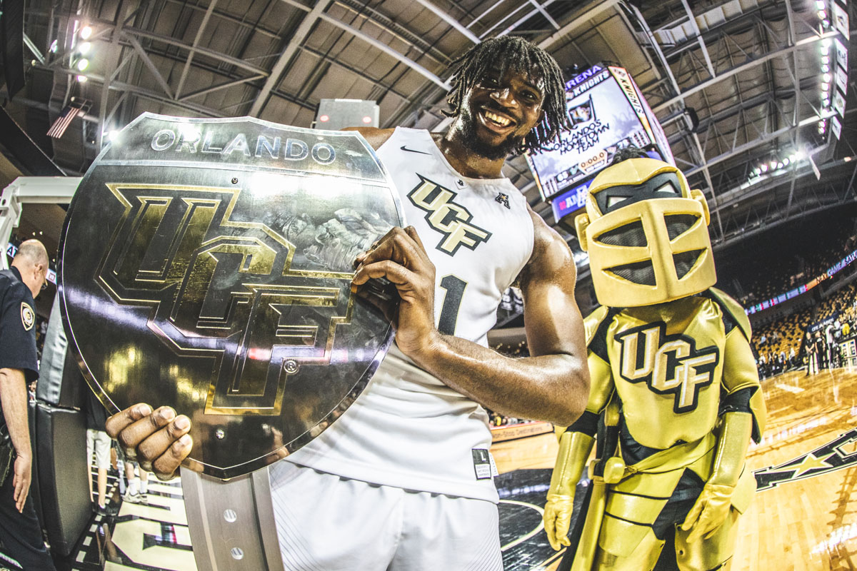 A UCF basketball player holds up a War-On-I-4 trophy with Knightro behind him.