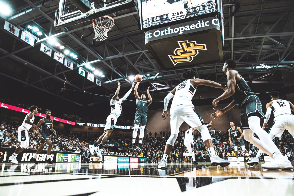 A UCF basketball player tries to stop a player from the opposing team from making a basket.