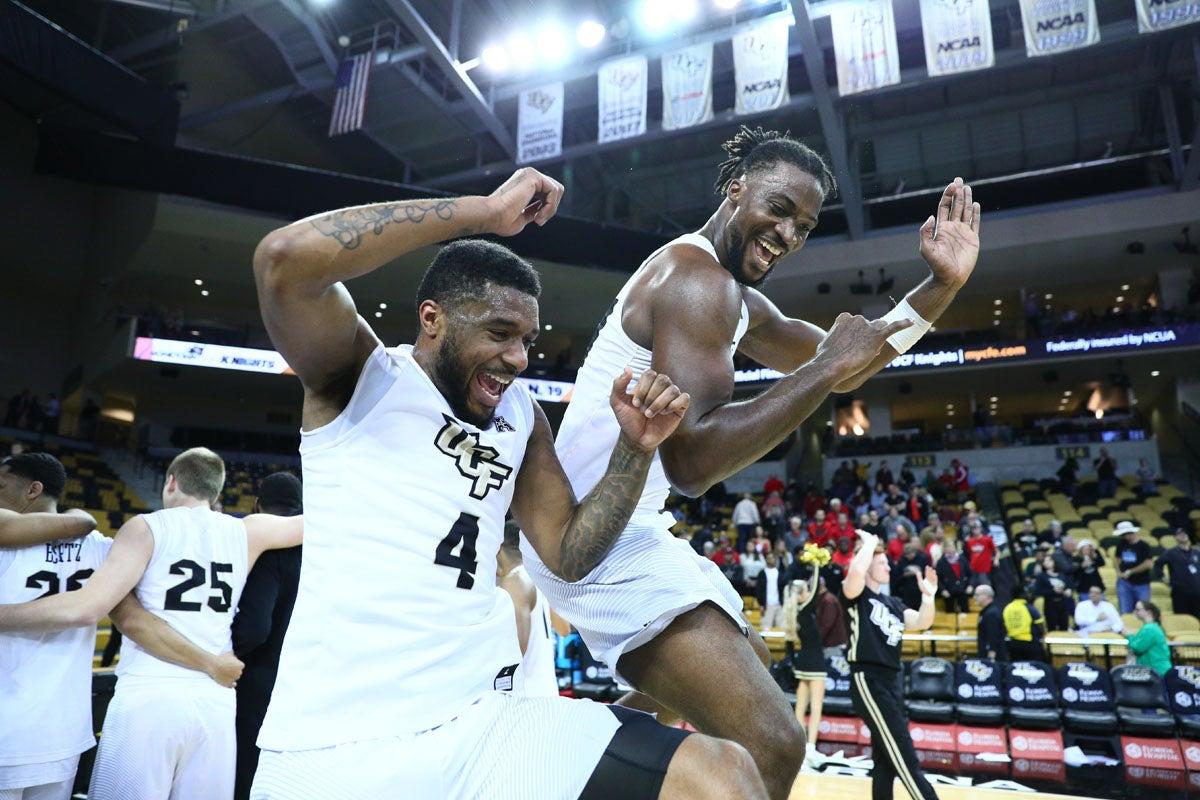 Two UCF basketball players celebrate.