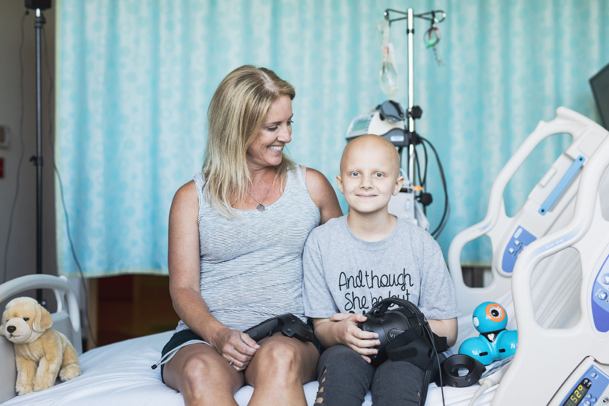 A young child in a hospital bed smiles and holds a VR headset while her mother looks at her.