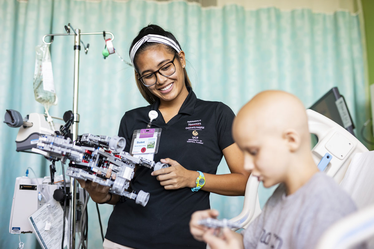 A UCF student volunteer smiles and holds a clipboard while watching a hospitalized child play.