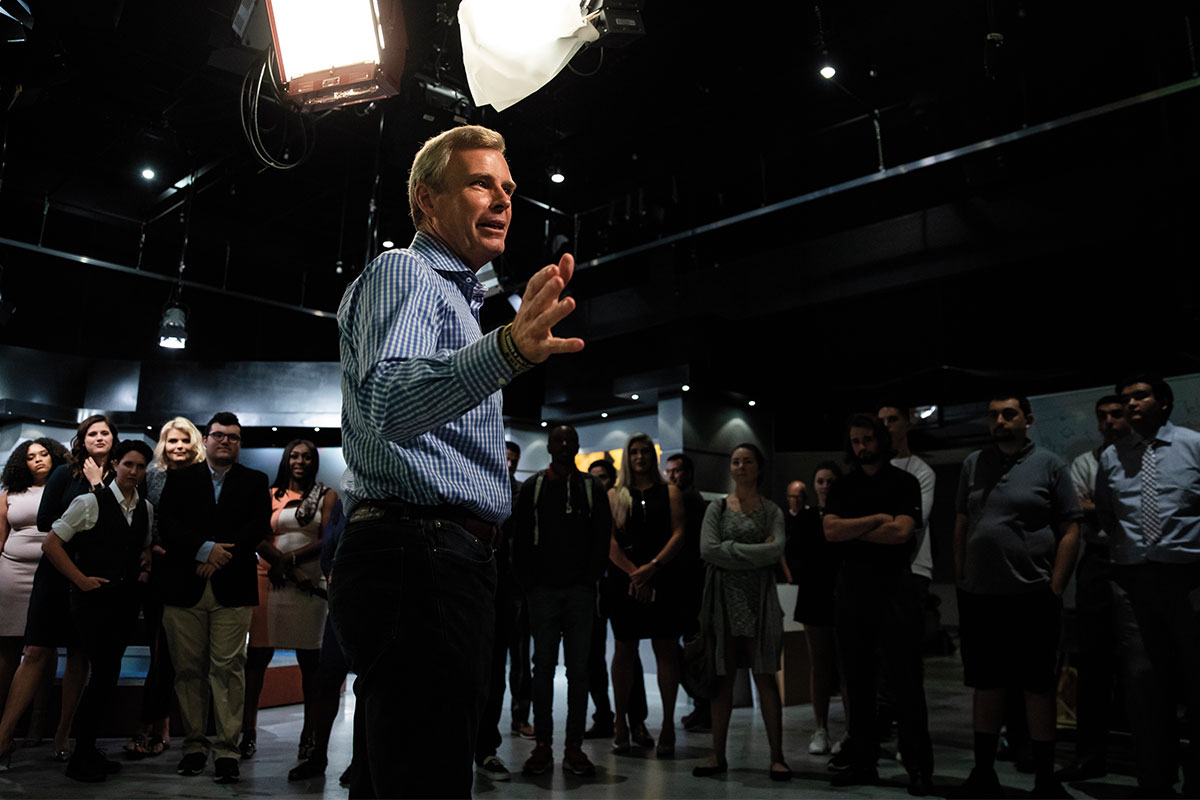 Tom Rinaldi speaks to a group of students in a dark studio.