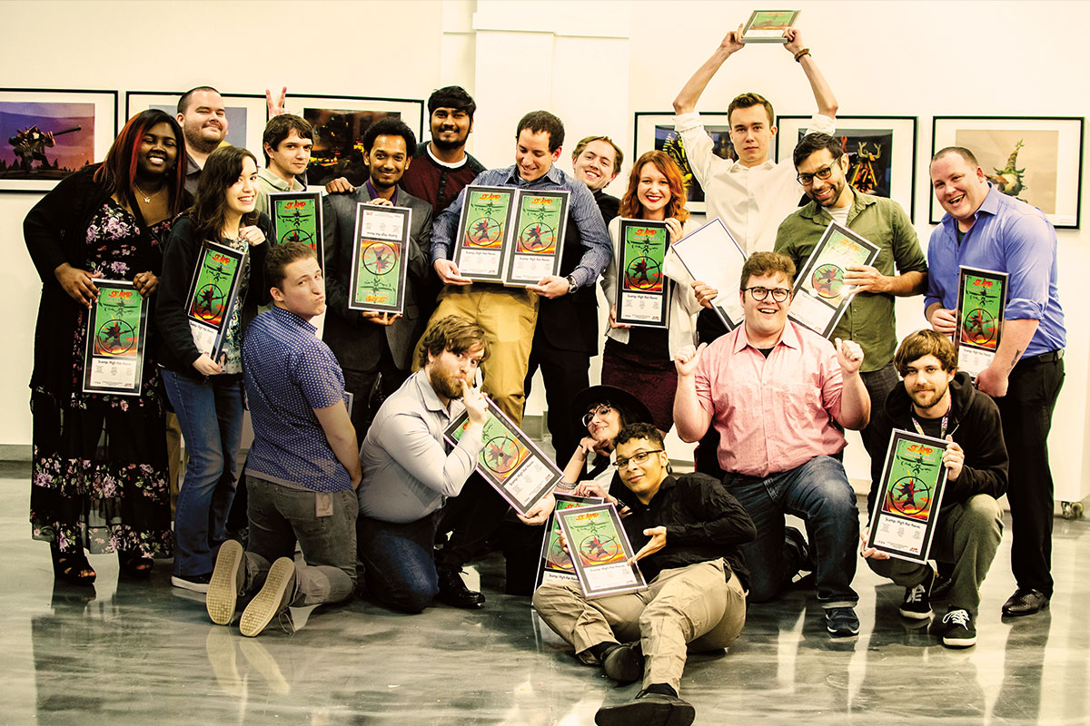A group of students in various poses hold up awards.