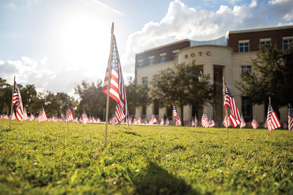 Small American flags decorate a green lawn outside the ROTC building.