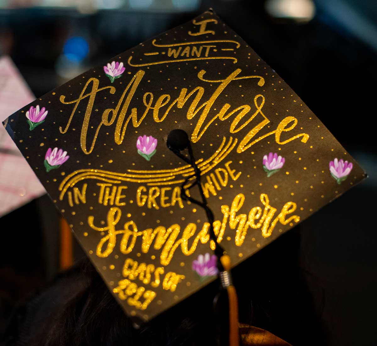 black graduation cap with gold lettering design: I want adventure in the great wide somewhere