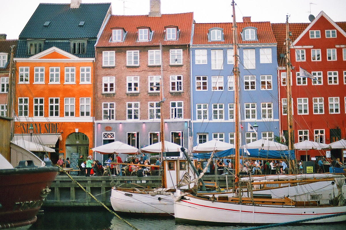 Boats sit on the water in front of some colorful buildings.