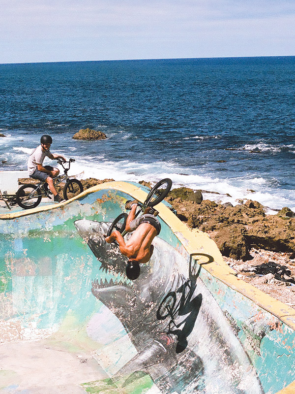 Two men ride BMX bikes in a concrete bowl by the ocean.