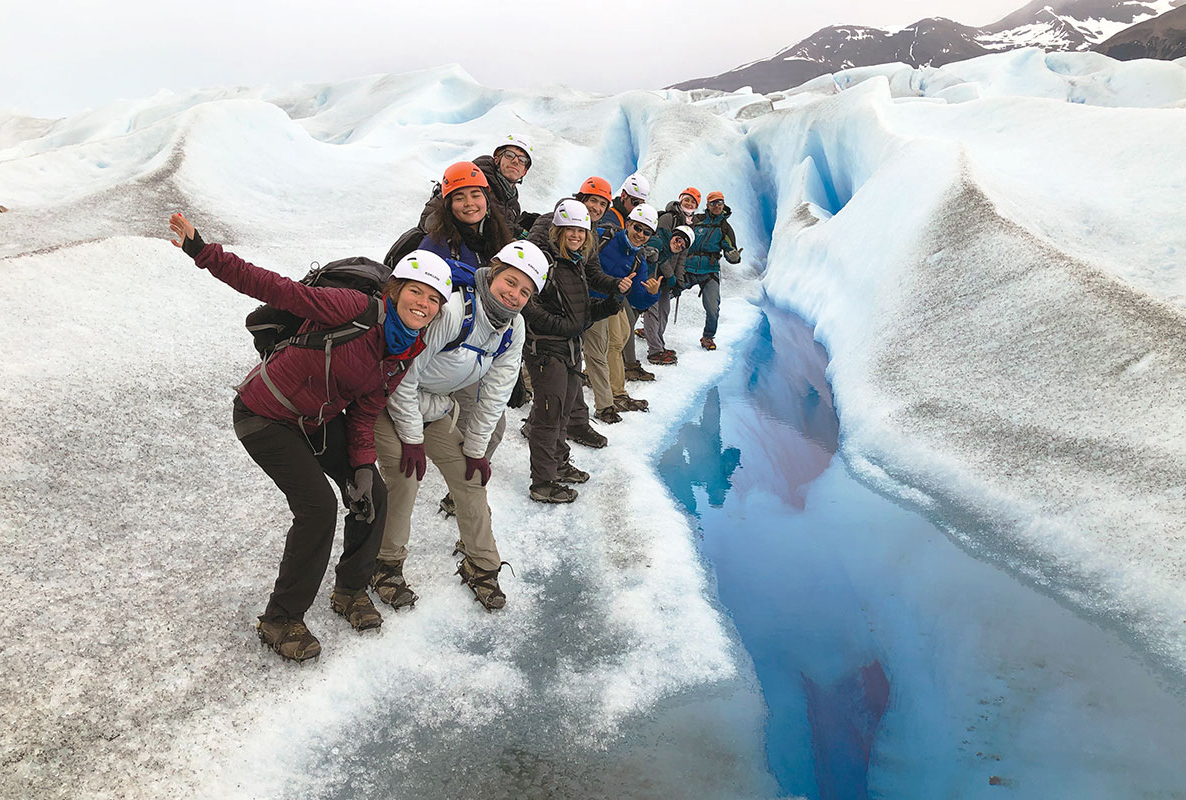 A group of people posing for a photo on a glacier.