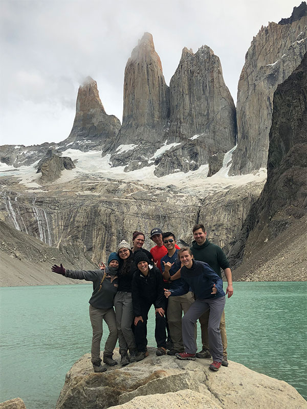 A group of people posing for a photo in front of mountains.