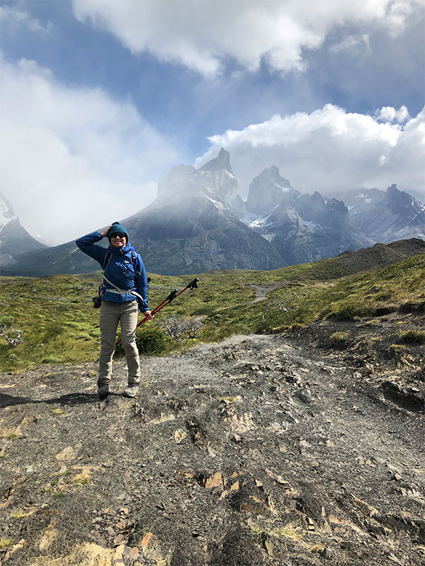 A man posing in front of a mountain.