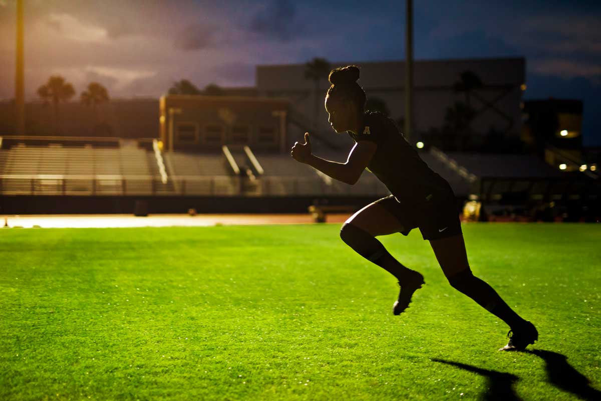 female soccer player takes off running on soccer field