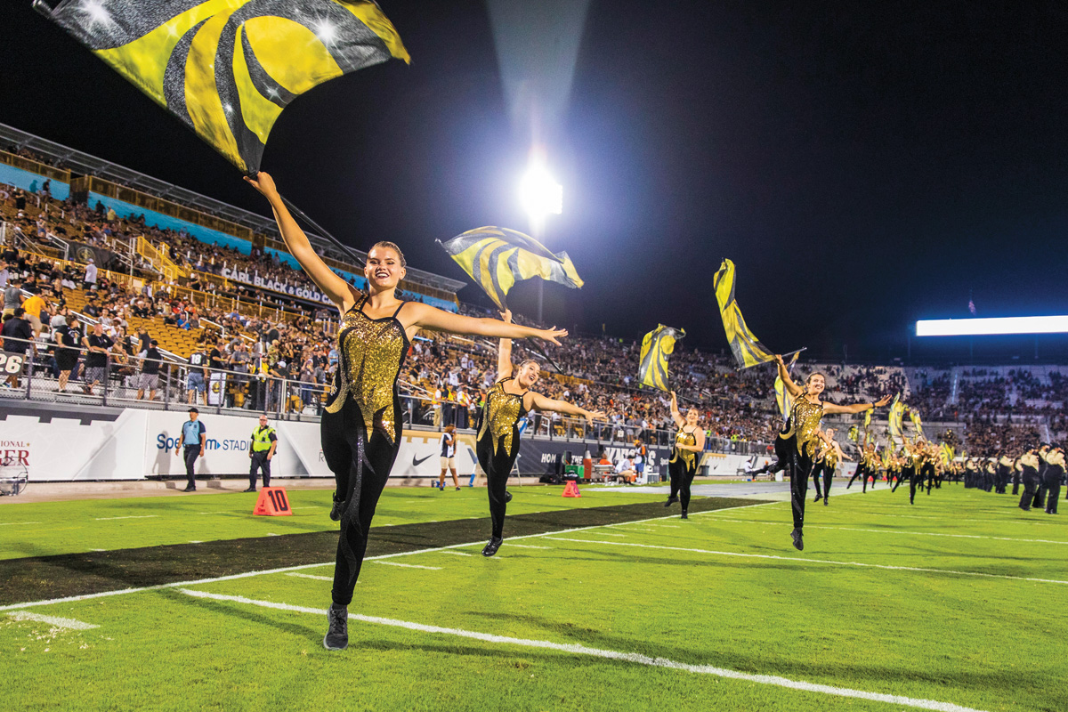 The color guard waves flags inside Spectrum Stadium.