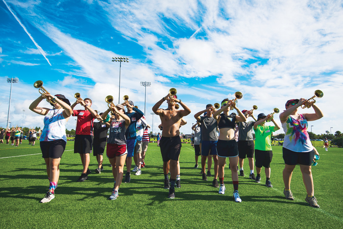 The trumpet section practices playing on a field.