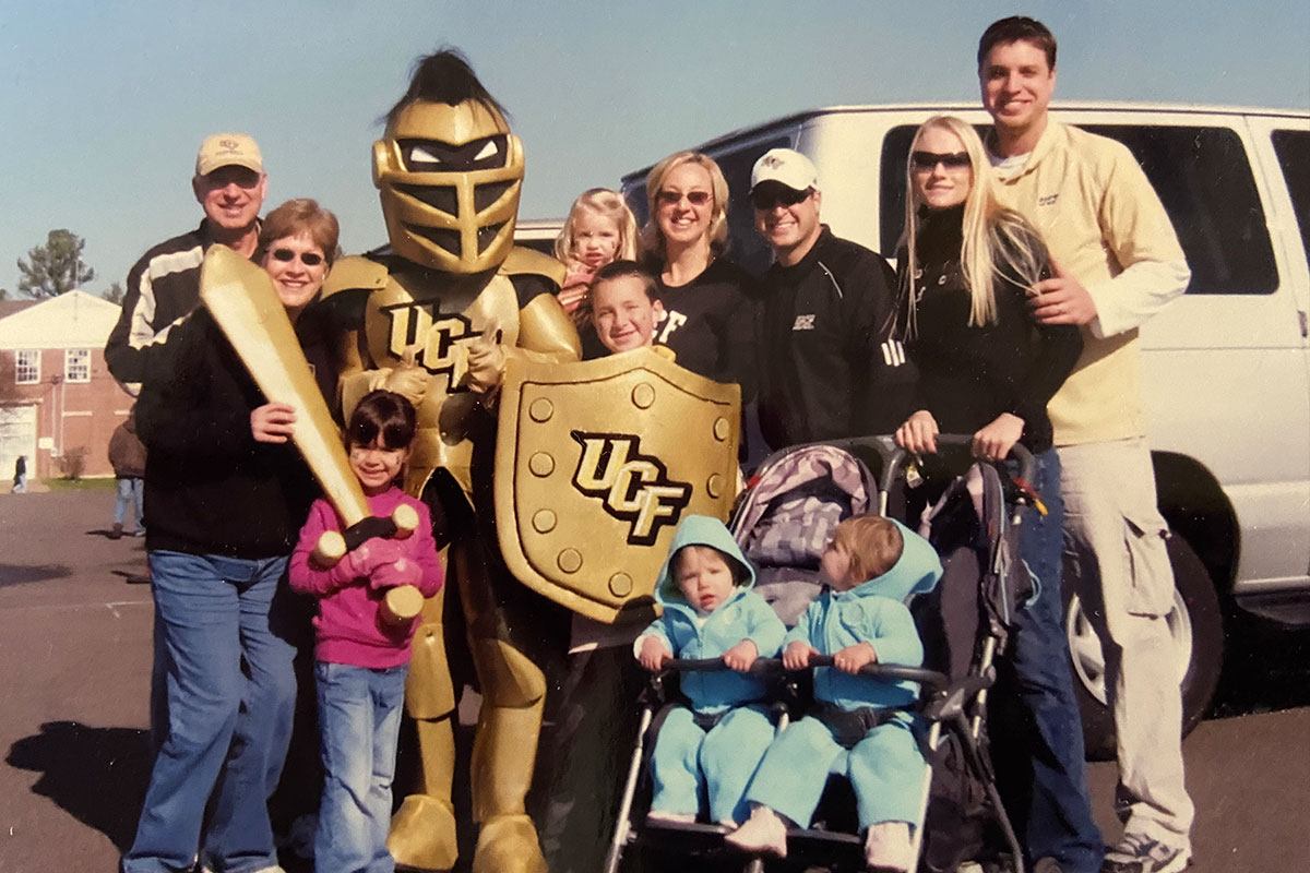 The Aliberti and Wright family pose for a photo with Knightro in a parking lot.