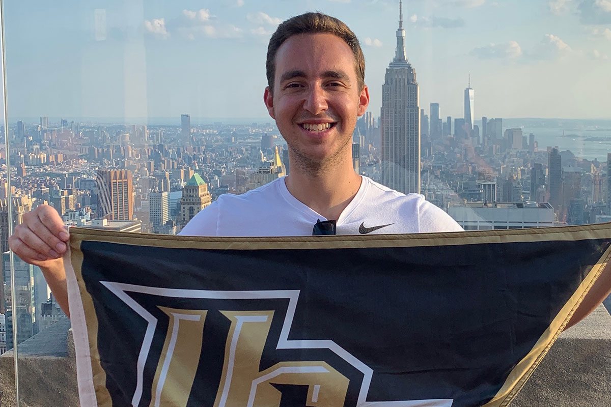 Brandon Aliberti holds a UCF flag while posing for a photo with a skyline behind him.