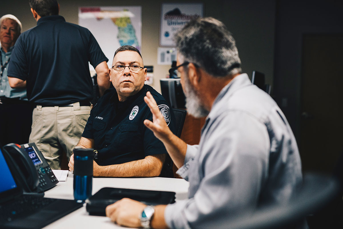 A male police officer and another man speak while sitting.