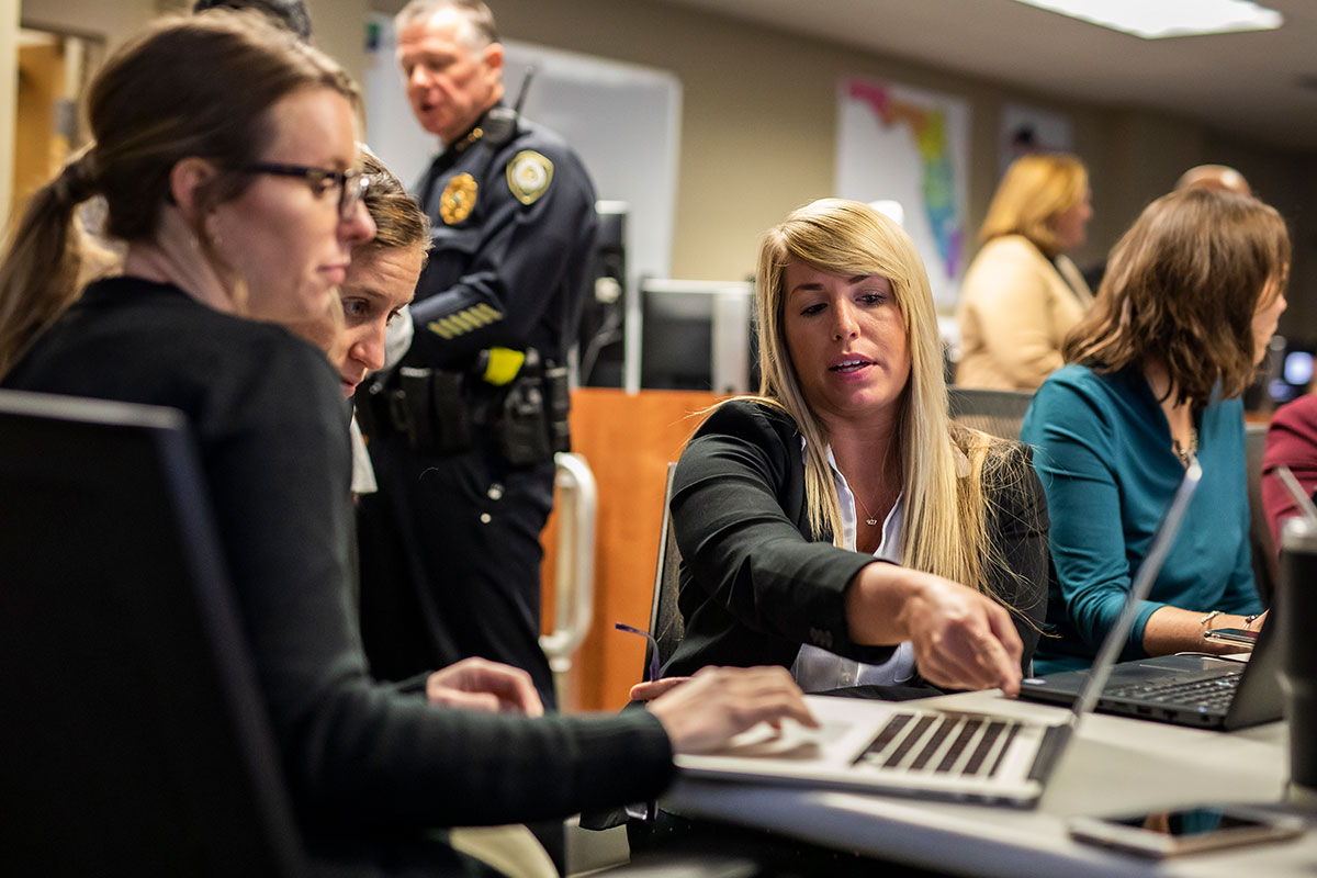 A woman points to a laptop screen while two women look at the screen.