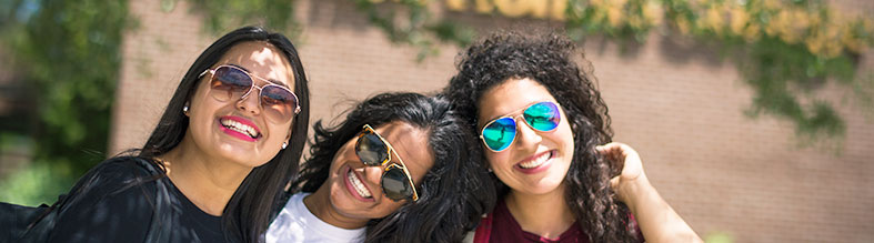 3 female ucf students wearing sunglasses while smiling at the camera